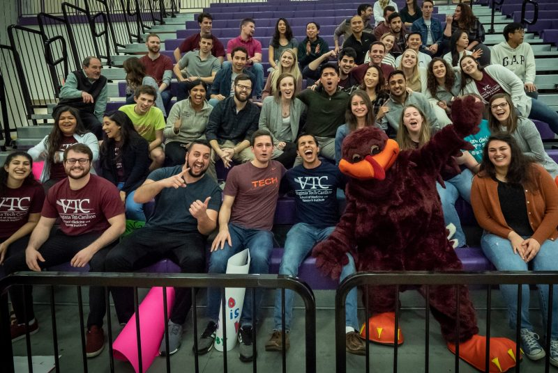 Students cheering in bleachers along with the Hokie Bird