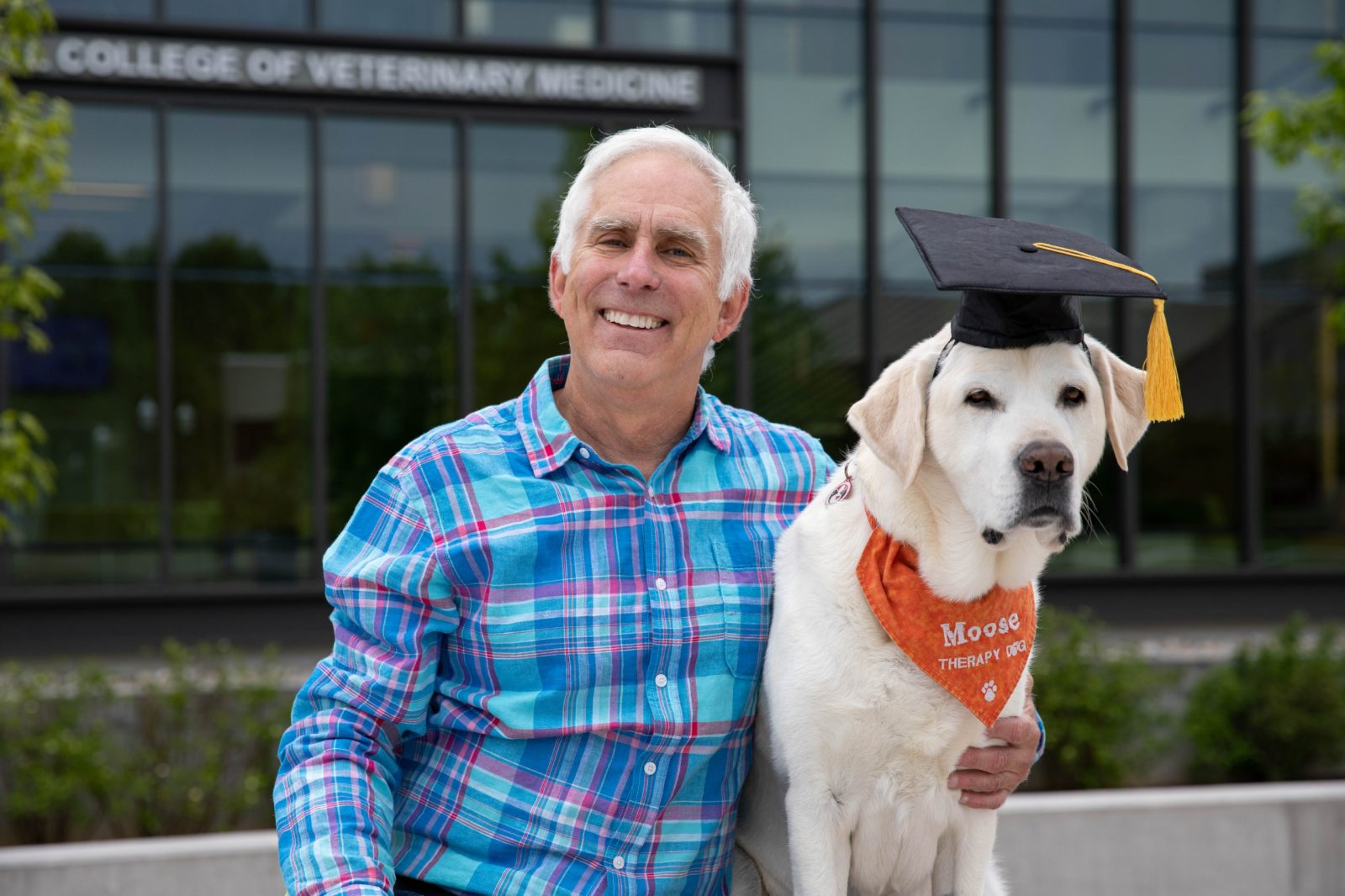 Moose, a yellow lab and therapy dog wearing a graduation cap, poses with owner/handler Trent Davis.
