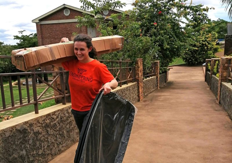 Brianna Friedman, a master's student in mechanical engineering, is wearing an orange VT mechanical engineering shirt and walking across a small bridge while carrying a box on her shoulder and other equipment, aircraft, and supplies in her hand.