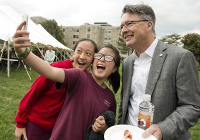 Members of the Hokie community take a picture with President Timothy Sands during the community pizza party on Dietrick Lawn.