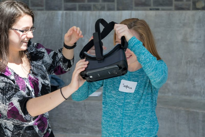 A woman helps a child put on a virtual reality headset